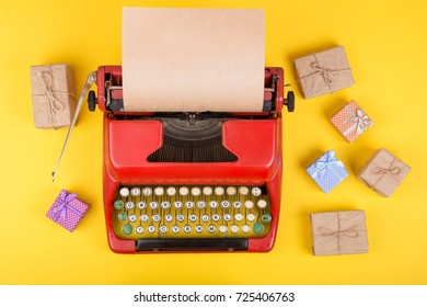 Holidays concept - red typewriter with blank craft paper, gift boxes on yellow background