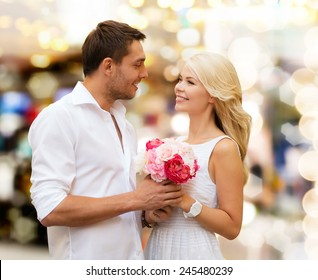holidays, dating, people and dating concept - happy couple with bunch of flowers over lights background