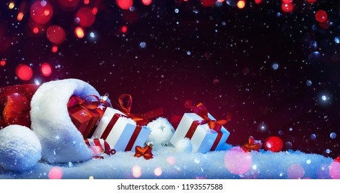 Holidays Decoration with Christmas Gifts on a Red Background with Colored Lights and Snow Effects