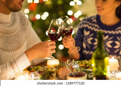 holidays, family and celebration concept - close up of happy couple having christmas dinner, drinking red wine and clinking glasses