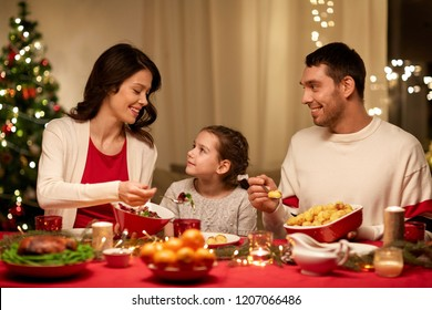 holidays, family and celebration concept - happy mother, father and little daughter having christmas dinner at home