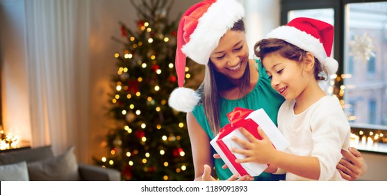 holidays and family concept - happy mother and daughter in santa hats with gift box over room with christmas tree background