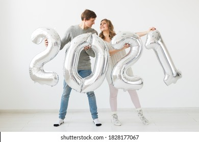 Holidays, festive and party concept - Happy loving couple holds silver 2021 balloons on white background. New Year celebration.