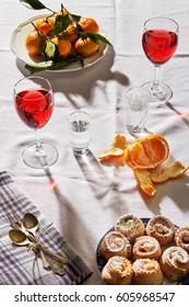 Holidays Food & drink: Fruits juices, Sweet alcohol beverage, orange citrus fruits  bakery. Orange, mandarin apples juices, still water & vodka, rum . Top view White background  Evening sunlight