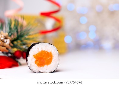 Holidays food. New Year Art. Real sushi with salmon. Christmas background. Red ribbons. Idea for menu, advertising, cafe, restaurant, or posters. Beautiful card, and tasty food