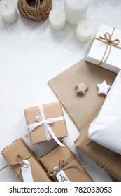Holidays Gifts. Christmas and New Year. Wrapping Decoration and Gift Boxes. Holiday Decorations Isolated on White Background. Holiday Scene with candles, present boxes. White and Brown Colors