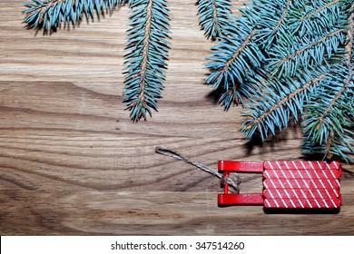 Holidays, gifts, new year, a sled and Christmas tree on the wooden background