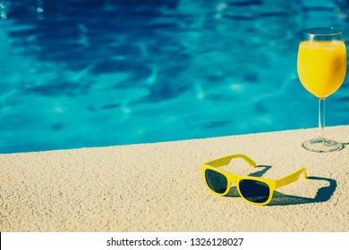 Holidays glamorous blogger kept women - idle lifestyle - poolside cocktail and sunglasses