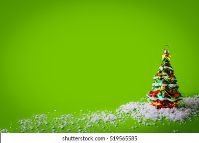 Holidays green greeting background with Christmas tree ornament, copy space.