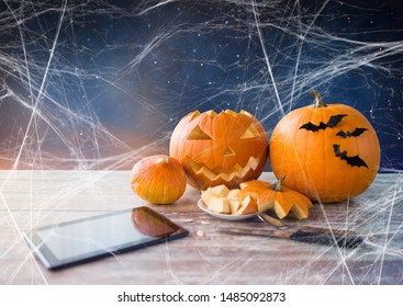 holidays, halloween and technology concept - jack-o-lantern or carved pumpkin, tablet pc computer, knife on wooden table and spiderweb over starry night sky background