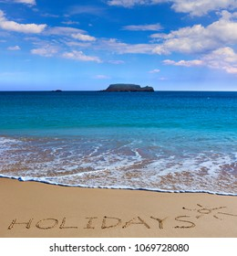 HOLIDAYS insctiption under the sun drawing on wet beach sand with the turquoisesea and the island on background. Summer season  vacation concept.