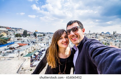 Holidays in israel, beautiful couple take a portrait photo selfie with cityscape of jerusalem behind