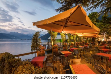 holidays in Italy - a view of a city Bellano, with the most  beautiful lake in Italy - Lago di Como in background. Area of famous Belano City at sunset. Restaurant with a view to lake