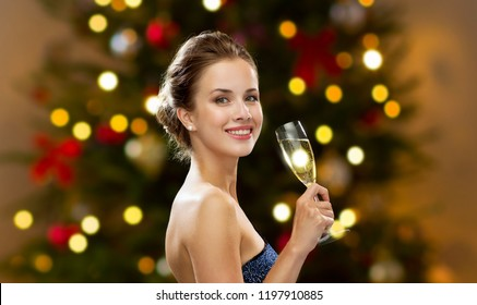 holidays, luxury and celebration concept - smiling woman in evening dress with glass of non-alcoholic champagne over christmas tree lights background
