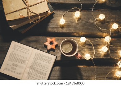 Holidays mood photo. Christmas lights and hot tea mug. Book for cosy evening. Sweet gingerbread and wooden heart on tray. Perfect winter flat lay. Hygge concept. Autumn warm and romantic background.