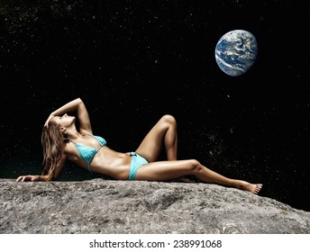 Holidays on the Moon. Woman lying on the ground in the night sky with the Earth. Elements of this image furnished by NASA.
