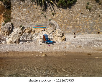 Holidays on the sea, silence and solitude. Relax lounger under sun umbrella against stone wall on the sea side.