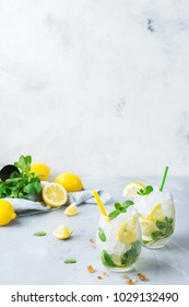 Holidays and party, food and drink concept. Cold alcohol mojito cocktail, long drink beverage, lemonade with lemon, mint and ice in a glass on a table. Copy space background