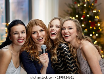 holidays, party and people concept - three women in evening dresses with microphone singing karaoke over room and christmas tree lights background