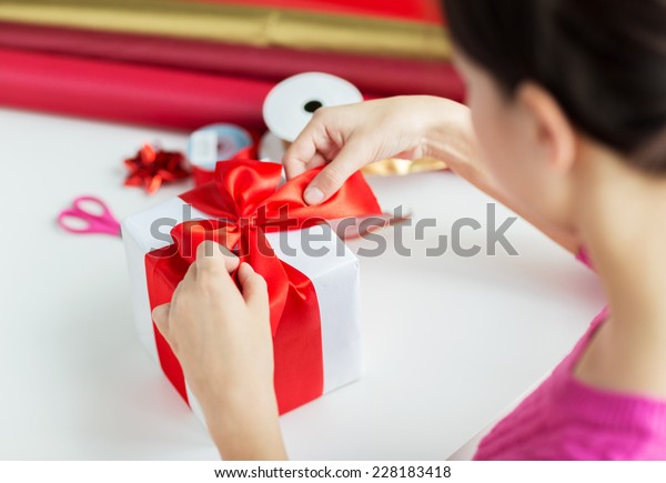 holidays, people and celebration concept - close up of woman decorating christmas present