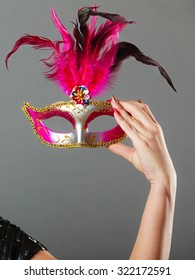 Holidays, people and celebration concept. Closeup woman hand holding carnival venetian mask on gray background.