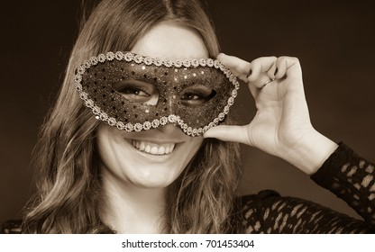 Holidays, people and celebration concept. Closeup woman face with carnival venetian mask on dark background, black and white photo