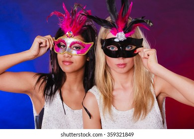 Holidays, people and celebration concept. two women mixed race and caucasian with carnival venetian masks over festive background.