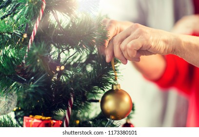holidays and people concept - close up of happy senior woman decorating christmas tree