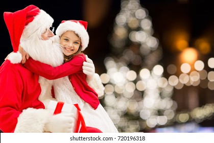 holidays and people concept - santa claus with happy little girl over christmas tree background