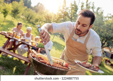 Holidays and people concept-happy family having lunch in garden.