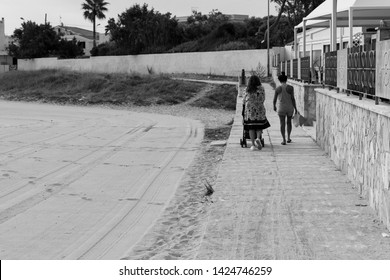 Holidays in Puglia, a region in the south of Italy. Mother and daughter take a walk with a stroller beside a beach on an isolated avenue.