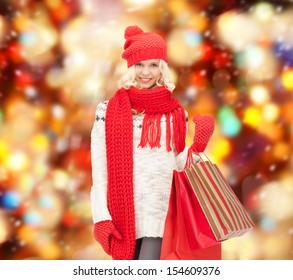 holidays, sale, christmas concept - beautiful teenage girl in winter clothes with shopping bags