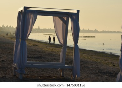 Holidays at sea. Covered altankas for relaxing on the seashore. Romantic atmosphere. People stroll along the seashore in the evening.