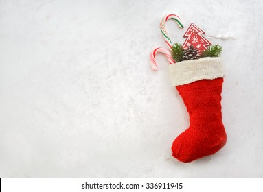 Holidays symbol stocking. Red christmas sock with gifts on a light background. Christmas background with copyspace