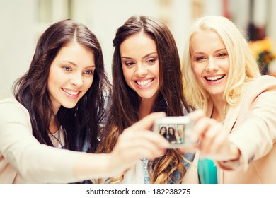 holidays and tourism concept - beautiful girls taking picture in cafe in city
