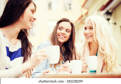 holidays and tourism concept - beautiful girls drinking coffee in cafe