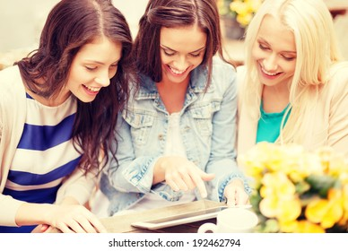 holidays, tourism, technology and internet - three beautiful girls looking at tablet pc computer in cafe outside