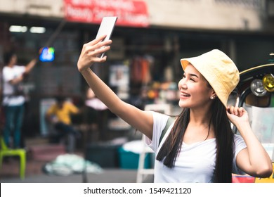 Holidays travel in city concept. Young asian happy woman in white shirt with backpack. Use smart phone selfie with tuktuk vintage style car. Beside landmark Khaosan street . Bangkok, Thailand