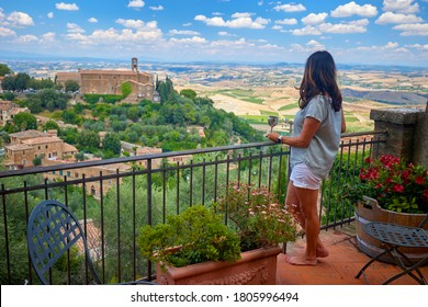 Holidays in Tuscany. Middle aged woman wearing a white dress watches the landscape of Tuscany from the terrace of a medieval house with a glass of wine in her hand. Montalcino, Italy.