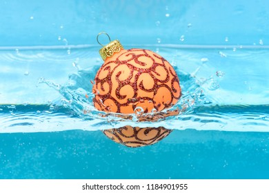 Holidays and vacation concept. Christmas decoration or toy for Christmas tree swim in pool. Festive decoration for Christmas tree, orange ball with glitter decor dropped into water, blue background.