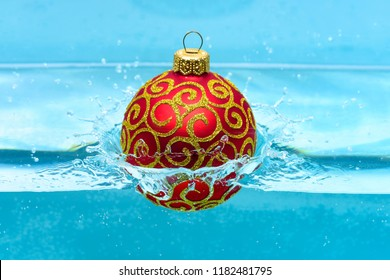 Holidays and vacation concept. Festive decoration for Christmas tree, red ball with glitter decor dropped into water, blue background. Christmas decoration or toy for Christmas tree swim in pool.