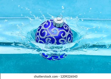 Holidays and vacation concept. Festive decoration for Christmas tree, blue ball dropped into water with splashes, blue background. Christmas decoration or toy for Christmas tree swim in pool.
