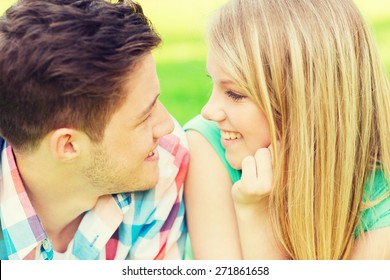 holidays, vacation, love and friendship concept - smiling couple looking at each other in park
