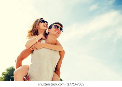 holidays, vacation, love and friendship concept - smiling couple having fun over sky background