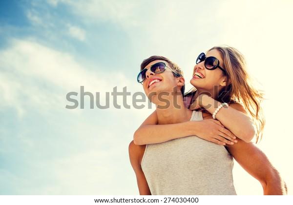 空の背景に楽しみを持つ笑顔のカップル、休暇、愛、友情のコンセプト