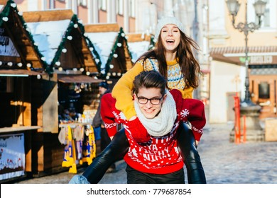 Holidays, vacation, love and relationship concept - Cheerful american couple playing piggyback ride in winter sunny day over Christmas fair market at central square of the european city.