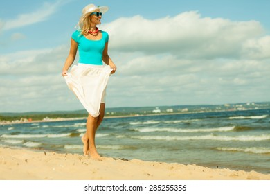 Holidays, vacation travel and freedom concept. Beautiful girl in summer clothing hat running on beach. Young woman having fun relaxing on the sea coast.
