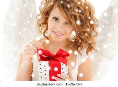holidays, xmas and costumes concept - happy teenage angel girl with christmas gift