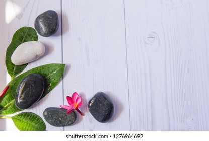 Holistic health concept. Top view of zen stones with  red plumeria flower and green leaves on white wooden table.
