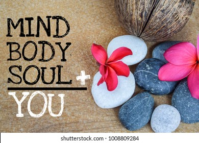 Holistic health concept of zen stones with deep red plumeria flower on wooden background. Text body mind soul equal you.